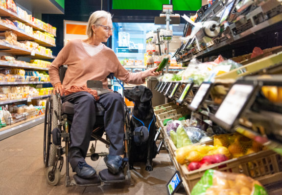 Assistance dog sits next to its keeper in a wheelchair, buying vegetables in the shop