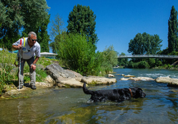 Blind dog keeper plays with his dog by the river